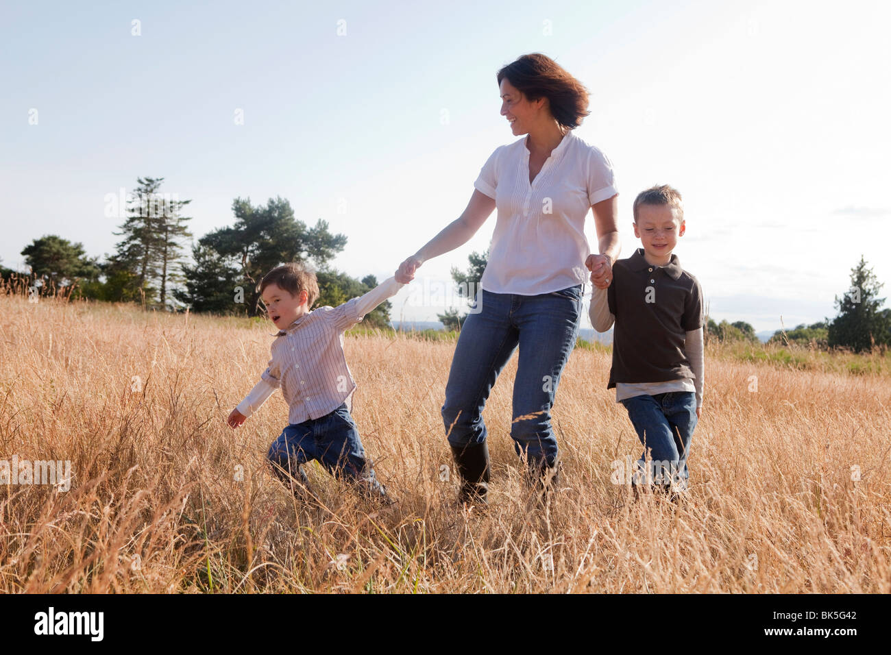 Mother and sons playing in field - Stock Image