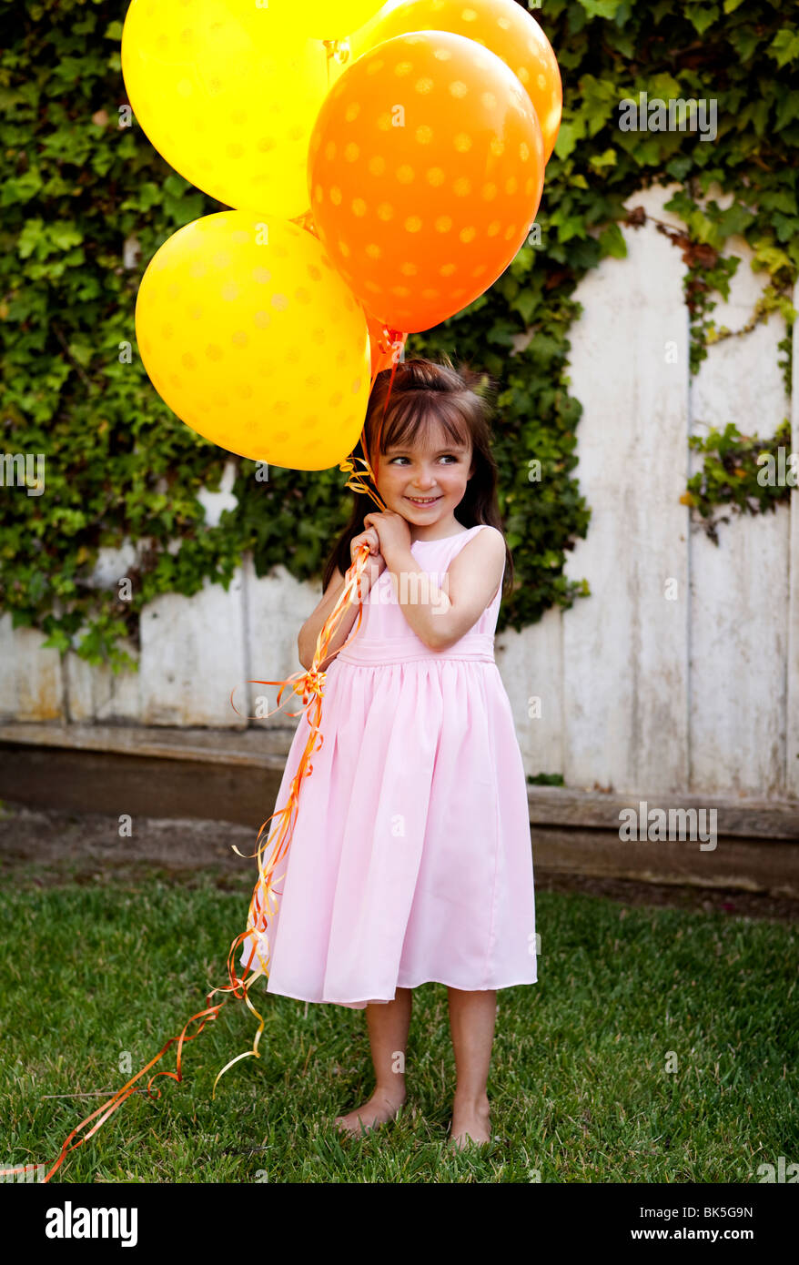 Young girl in sundress with bunch of balloons - Stock Image