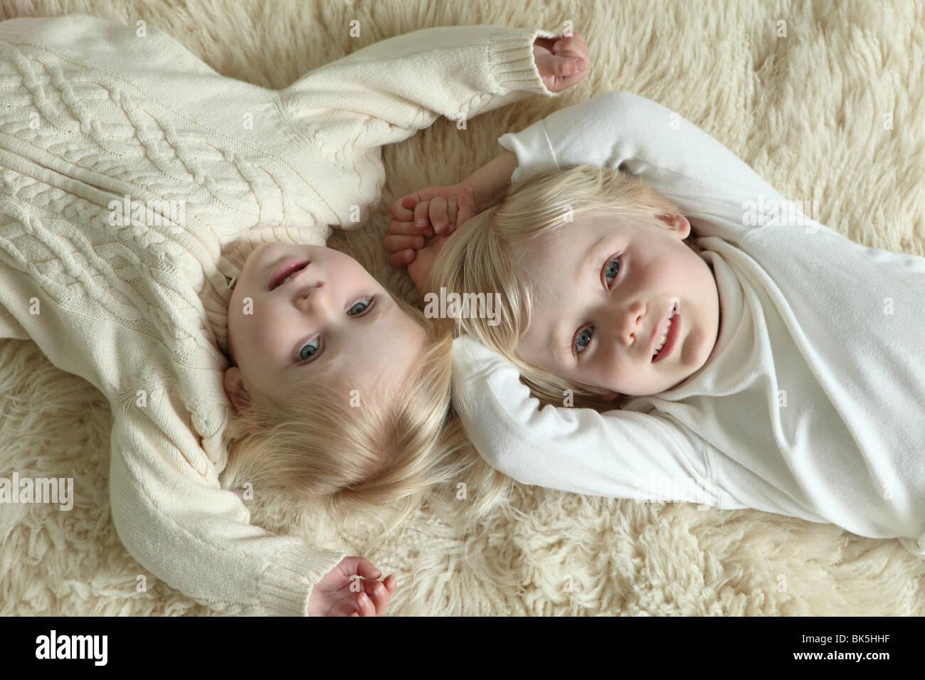 Brother and sister laying on sheepskin rug - Stock Image