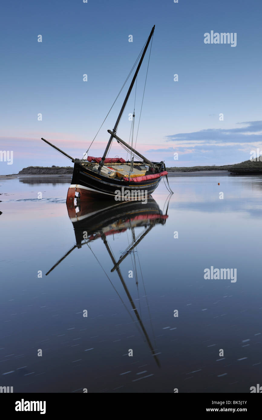 Old ketch reflecting in Aln Estuary as tide rises, Alnmouth, Northumberland, England, United Kingdom, Europe - Stock Image