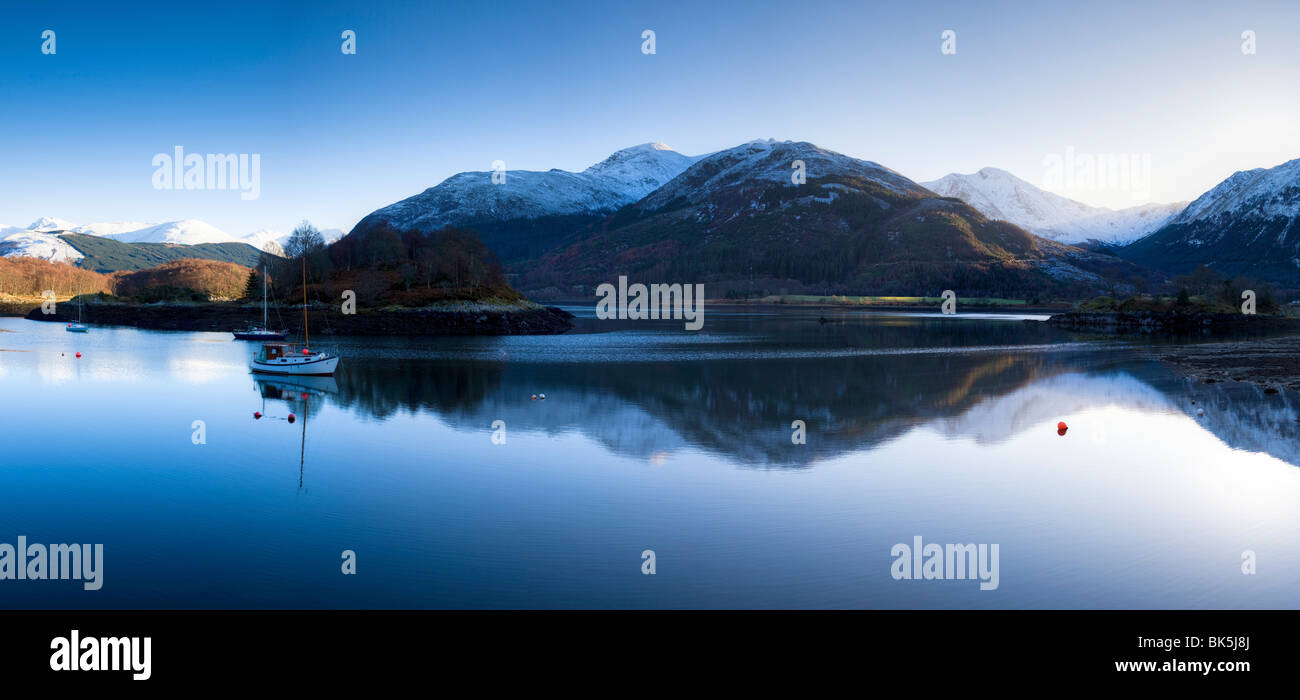 Winter view of flat calm Loch Leven with snow covered mountains reflected, near Ballachulish, Glencoe, Highland, - Stock Image