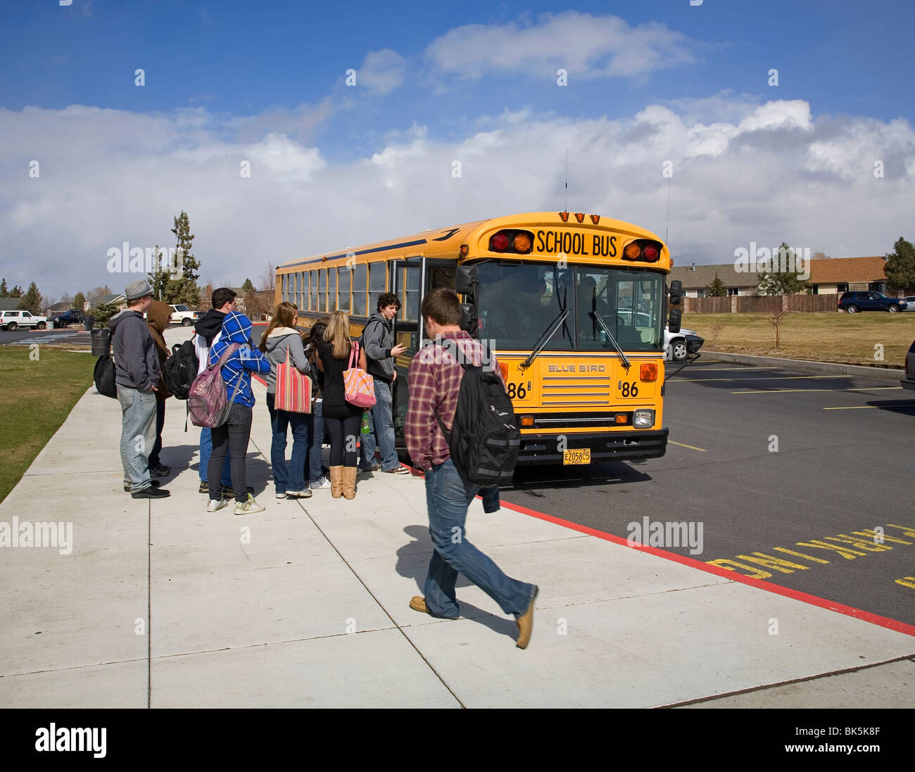 High school students board a school bus for the afternoon trip home after school - Stock Image