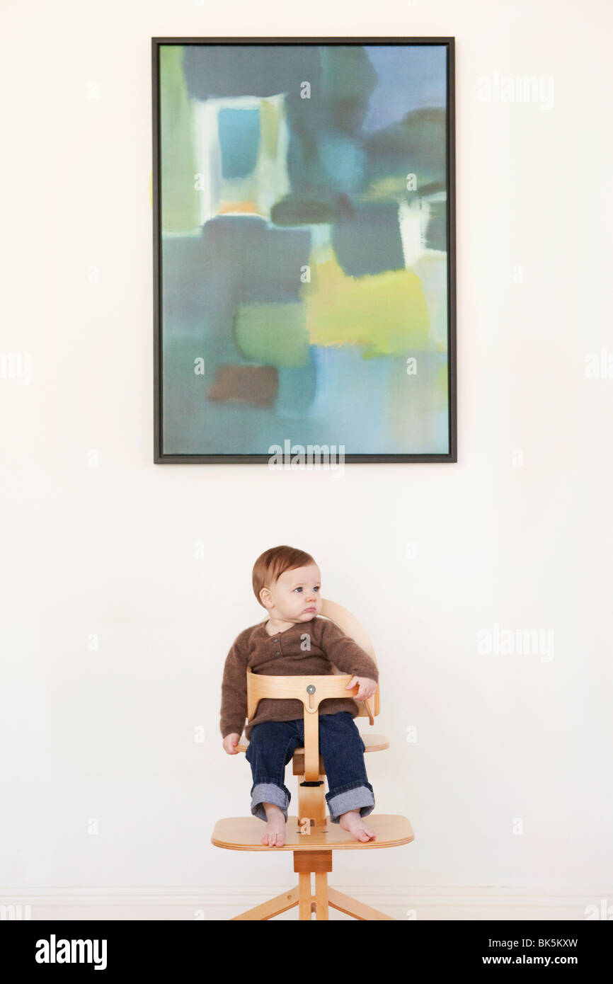 Little boy in wooden high chair - Stock Image