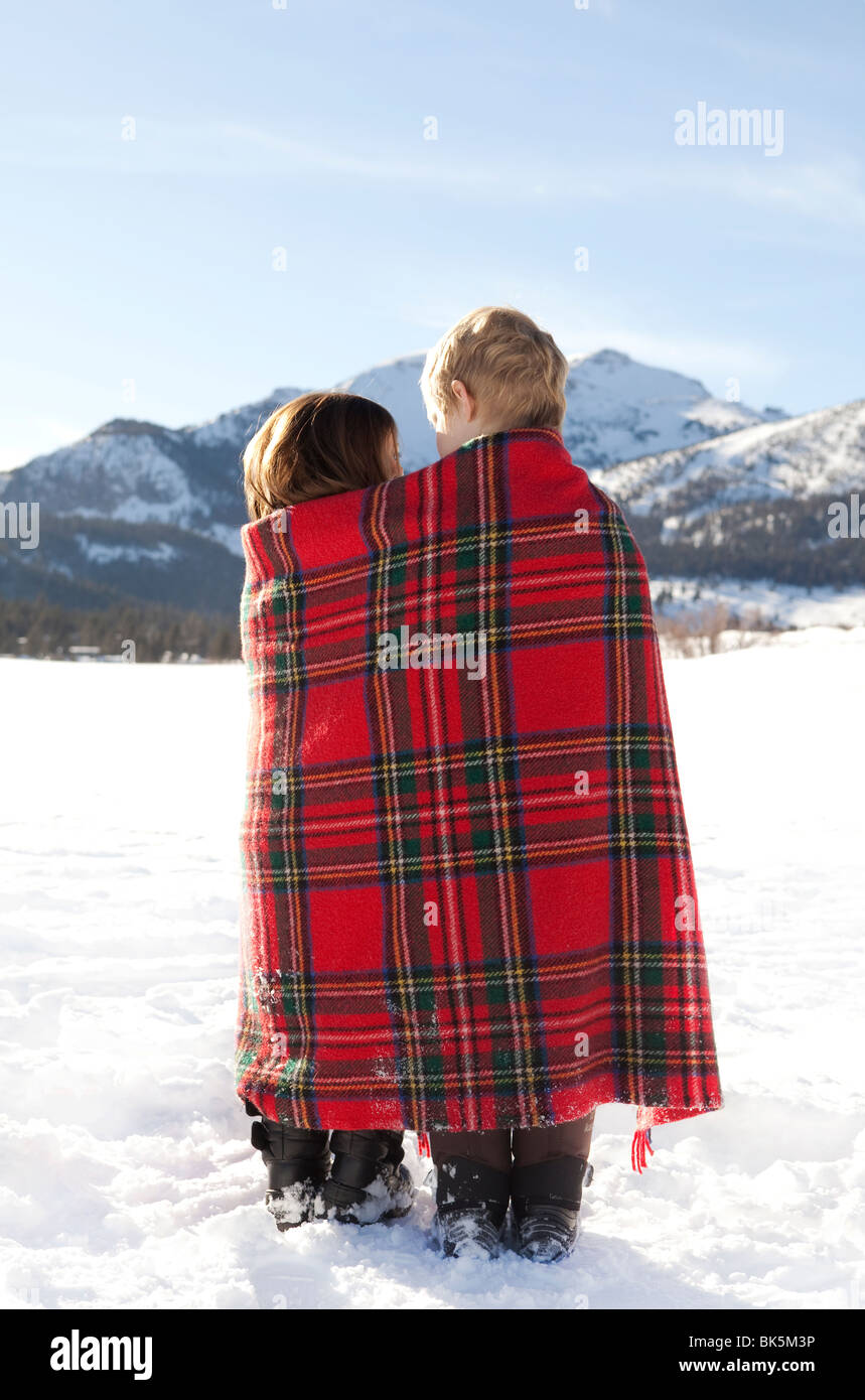 Boy and girl wrapped in red plaid blanket in the snow - Stock Image