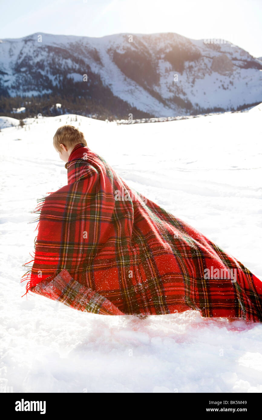 Young boy wrapped in red plaid blanket playing in snow - Stock Image