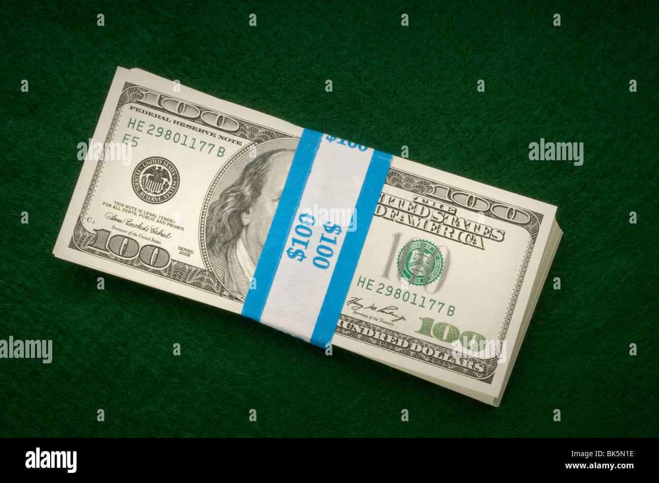 stacks of money on green - Stock Image