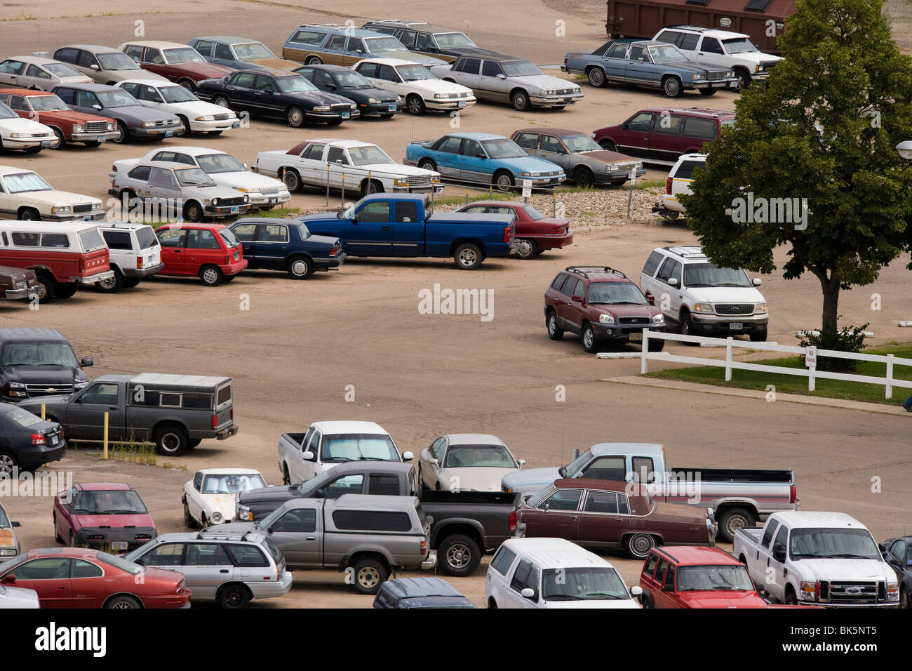 Parking lot outside of a US factory. Mostly older cars, not very well maintained. Nebraska, American Mid West. - Stock Image