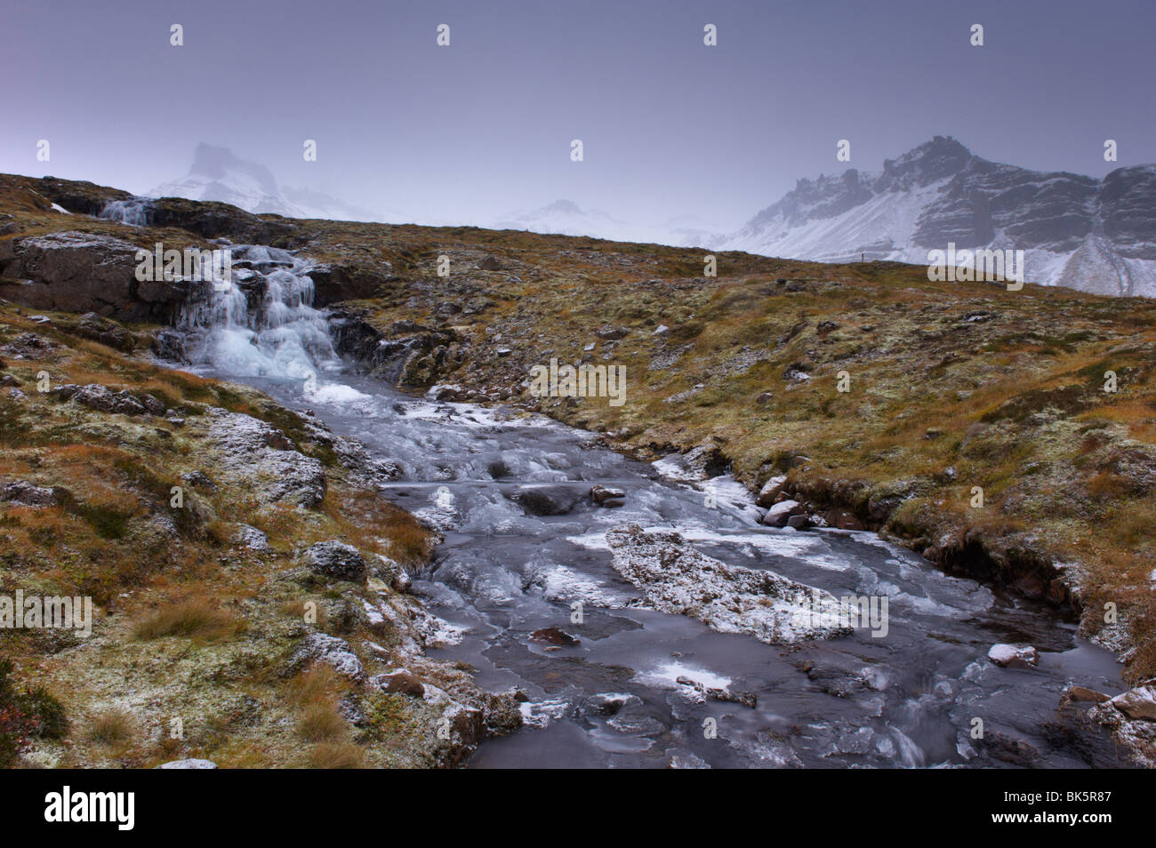 Frozen waterfall and stream in the East Fjords, near Neskaupstadur, Nordfjordur-Reydarfjordur, East Fjords, Iceland - Stock Image