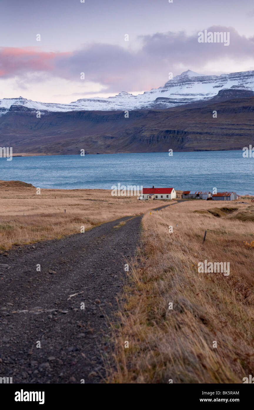Red-roofed house and snow-capped mountains in Reydarfjordur fjord, East Fjords, Iceland, Polar Regions - Stock Image
