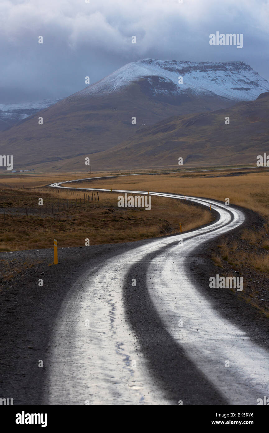 Road and landscape in Vatsnes Peninsula, with snow-covered mountains in October, north coast of Iceland, Iceland, - Stock Image