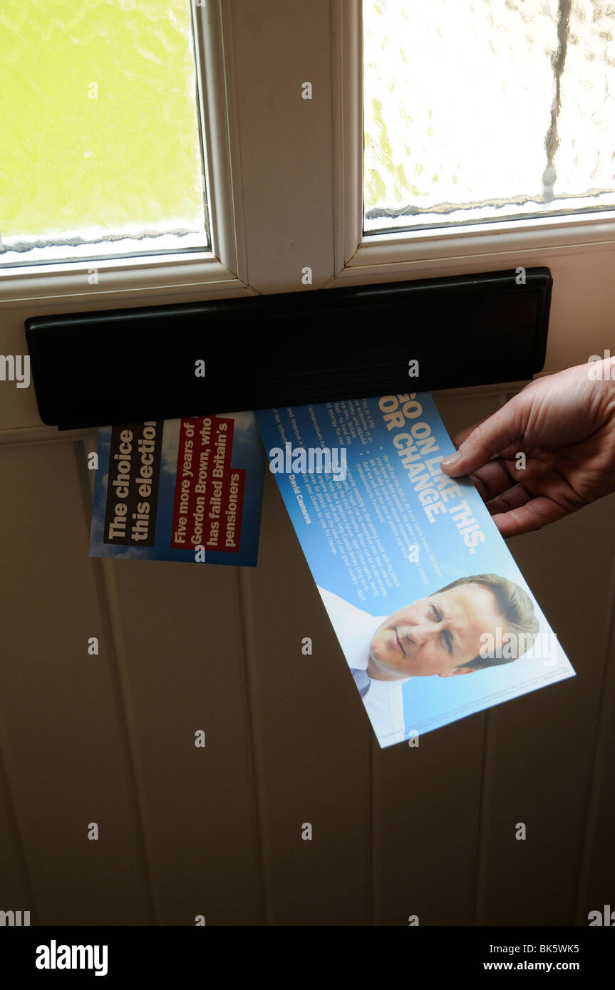 Tory party election flyer featuring David Cameron in the letterbox of a prospective voter - Stock Image