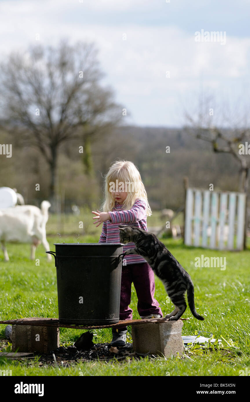 Stock photo of a four year old child playing make believe games in the garden with her cat. - Stock Image