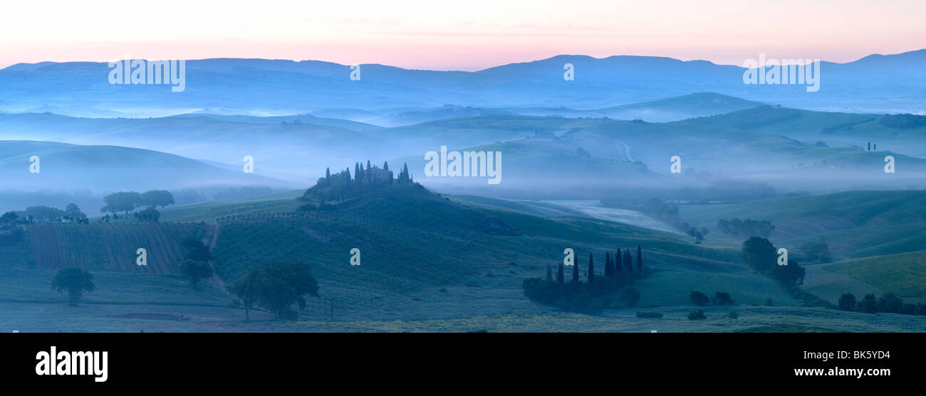 Misty dawn panoramic view across Val d'Orcia, UNESCO World Heritage Site, San Quirico d'Orcia, near Pienza, - Stock Image