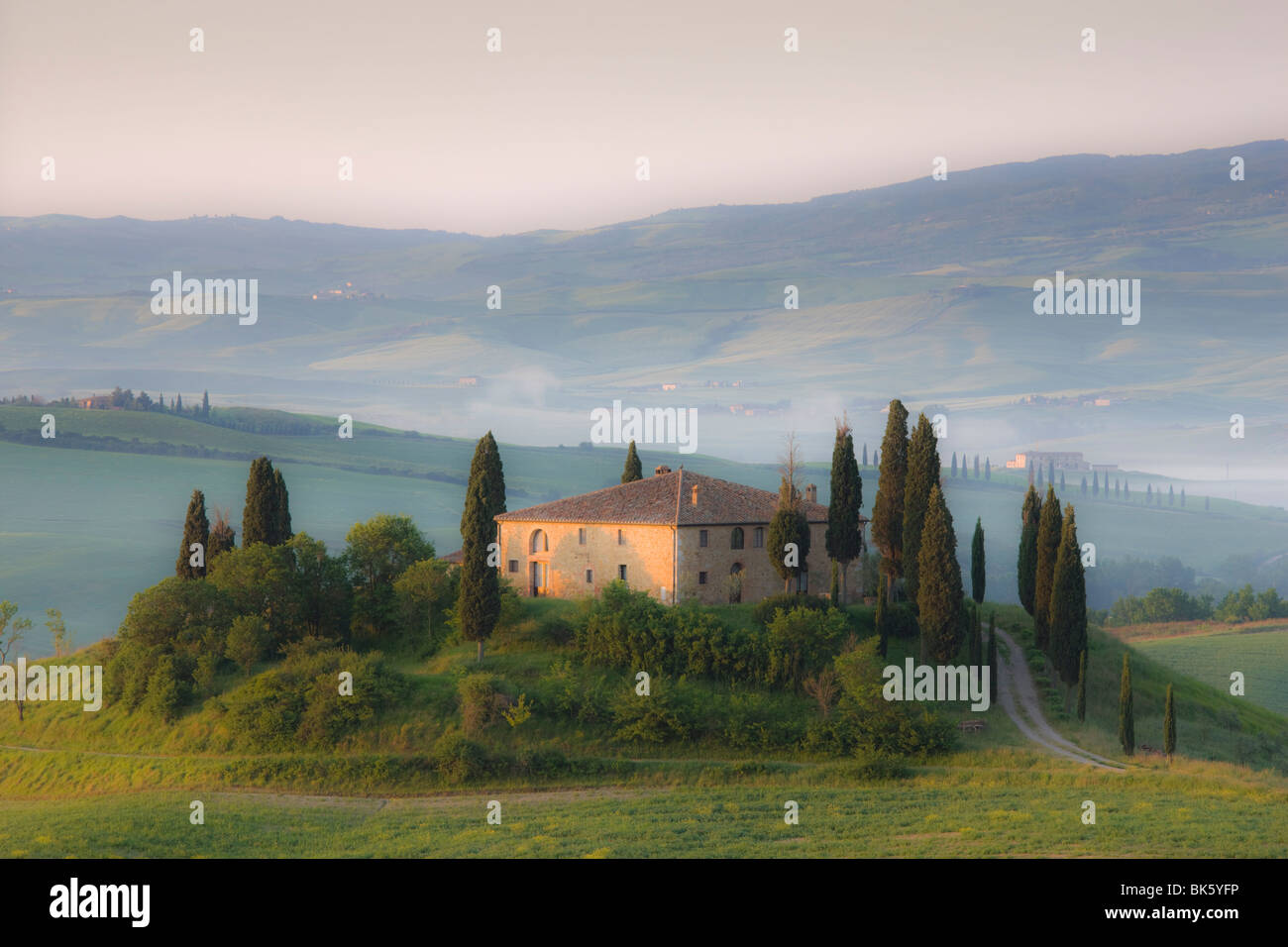 Misty dawn view across Val d'Orcia, UNESCO World Heritage Site, San Quirico d'Orcia, near Pienza, Tuscany, Italy Stock Photo