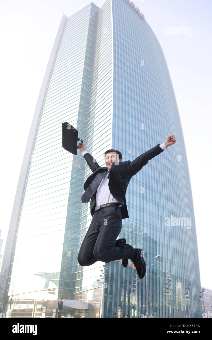 businessman jumping in front of tall building stock photo 29021730