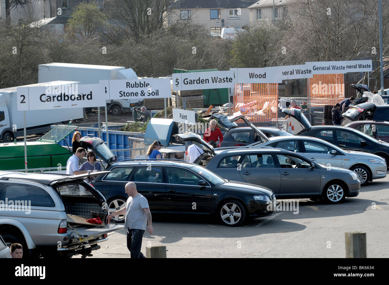 People recyling rubbish and waste at council recycling centre - Stock Image