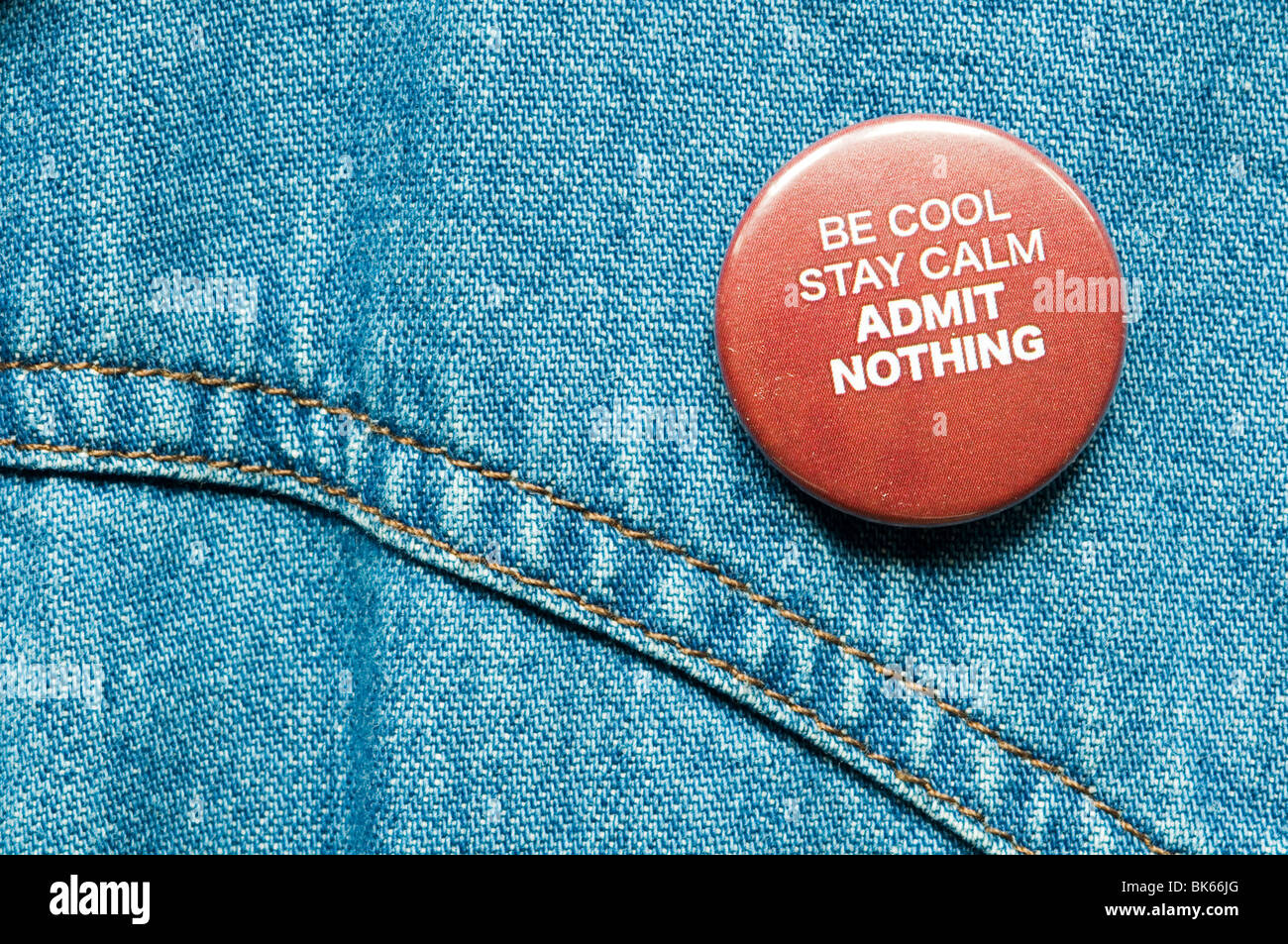 Be Cool Stay Calm Admit Nothing badge on denim jacket - Stock Image