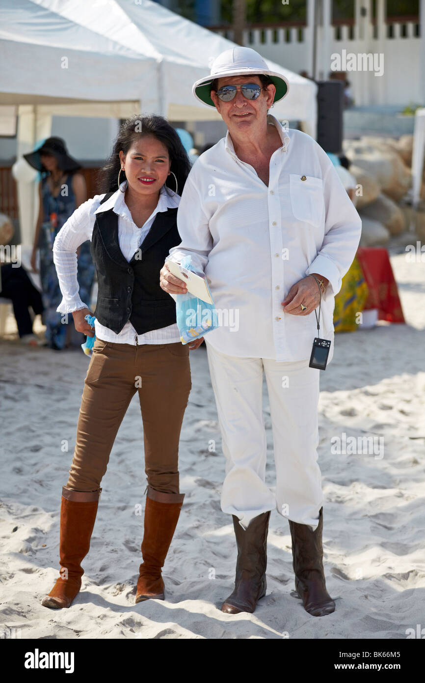 Young Asian woman and older Caucasian man. Married couple at a beach event. Thailand S. E. Asia - Stock Image