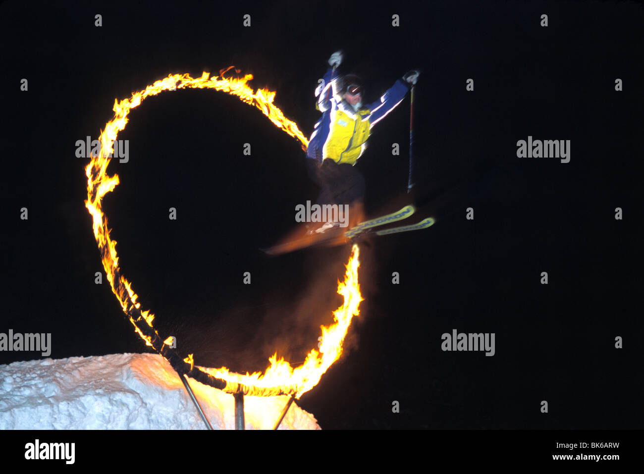 snow skier jumps through ring of fire at night - Stock Image