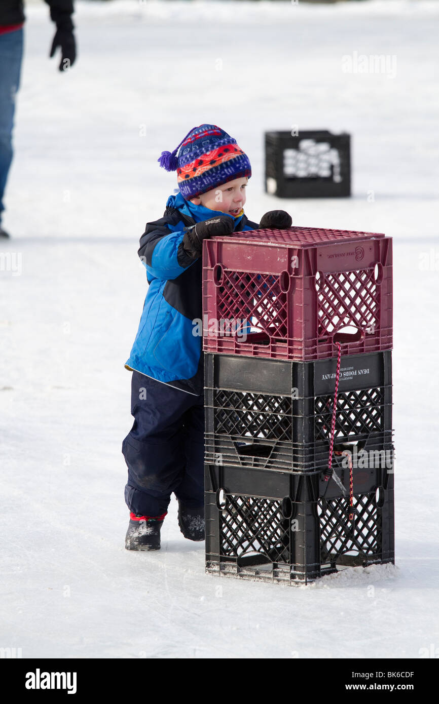Young boy learning to ice skate winter - Stock Image