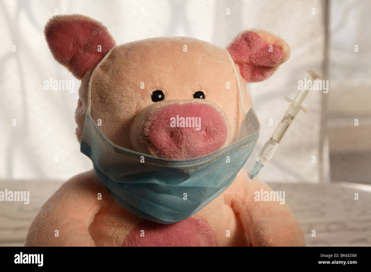 Toy pig with a syringe in the shoulder, head shot. - Stock Image