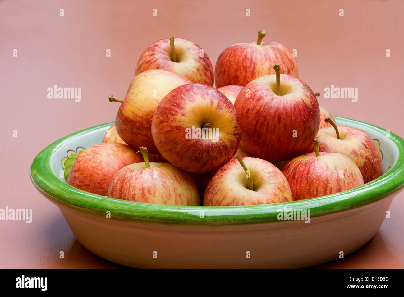 Close-up red apples on peachy background - Stock Image