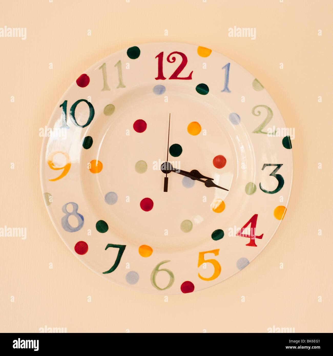 A Polka dot patterned clock by Emma Bridgewater decorated by hand hanging on a wall - Stock Image