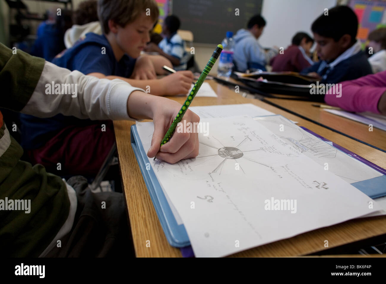 Left handed student draws on white paper with green pencil in classroom at Kealing Middle School in Austin, Texas, - Stock Image
