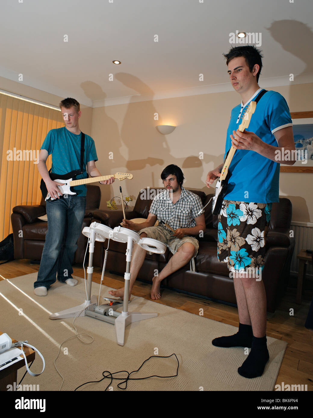 Teenagers playing Rock Band computer game. - Stock Image