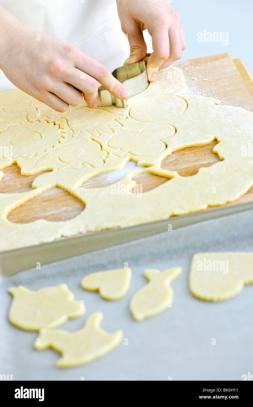 Woman using cookie cutter and baking homemade cookies - Stock Image