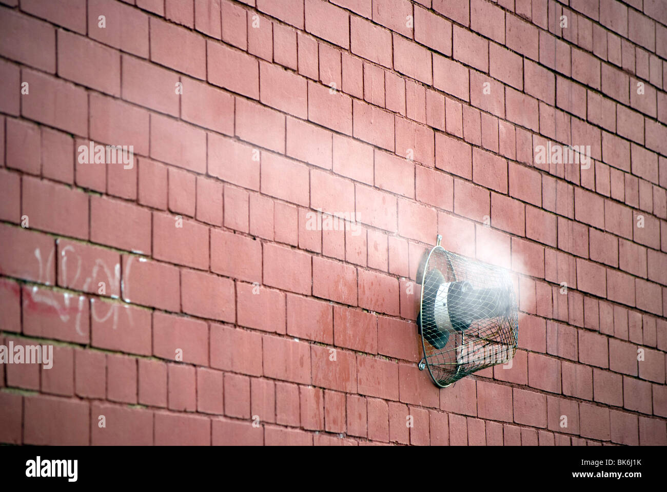 Steam rising from a gas central heating vent in the wall of a building. - Stock Image