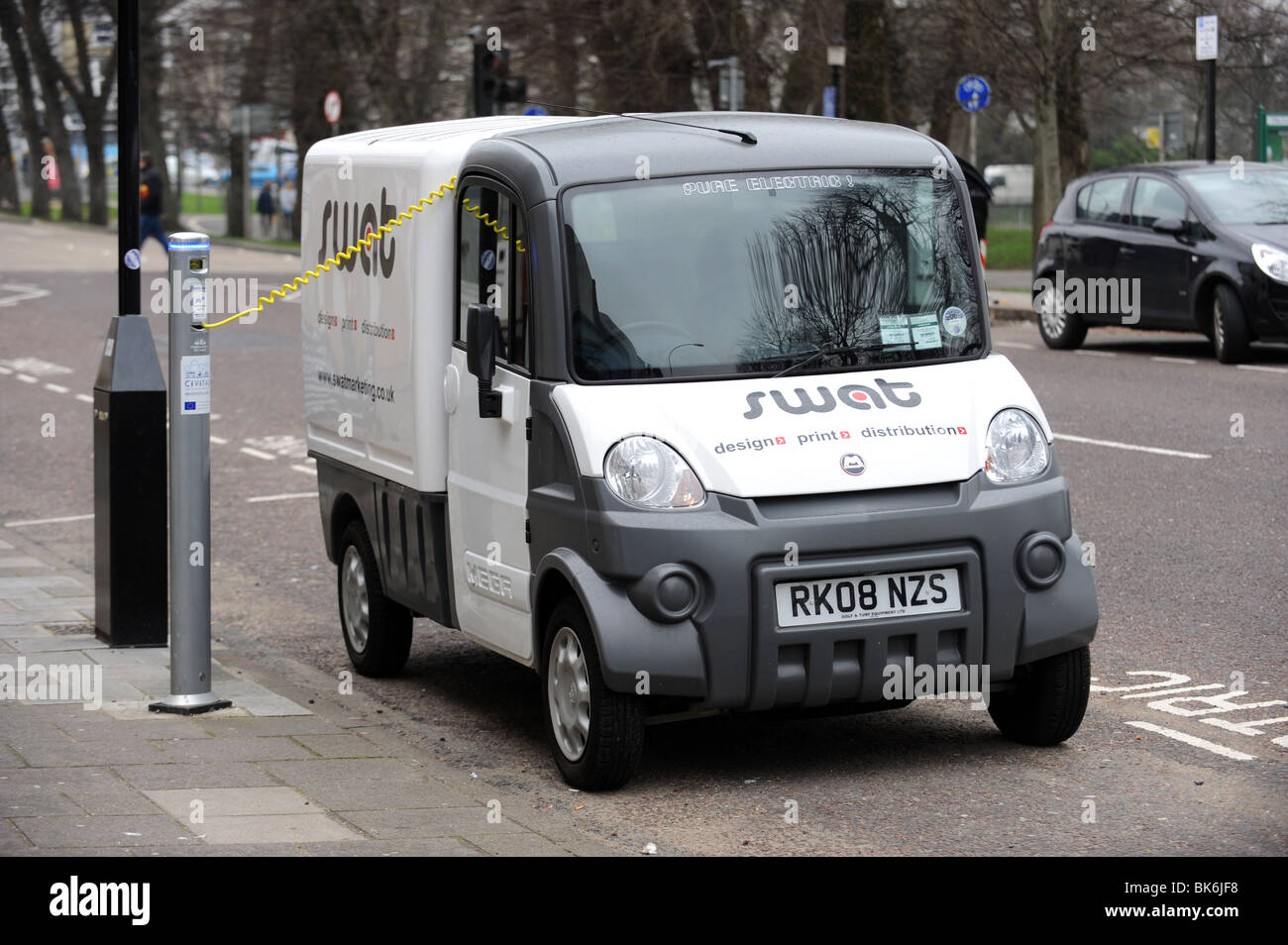 An electric van recharges at a charging point in Brighton - Stock Image
