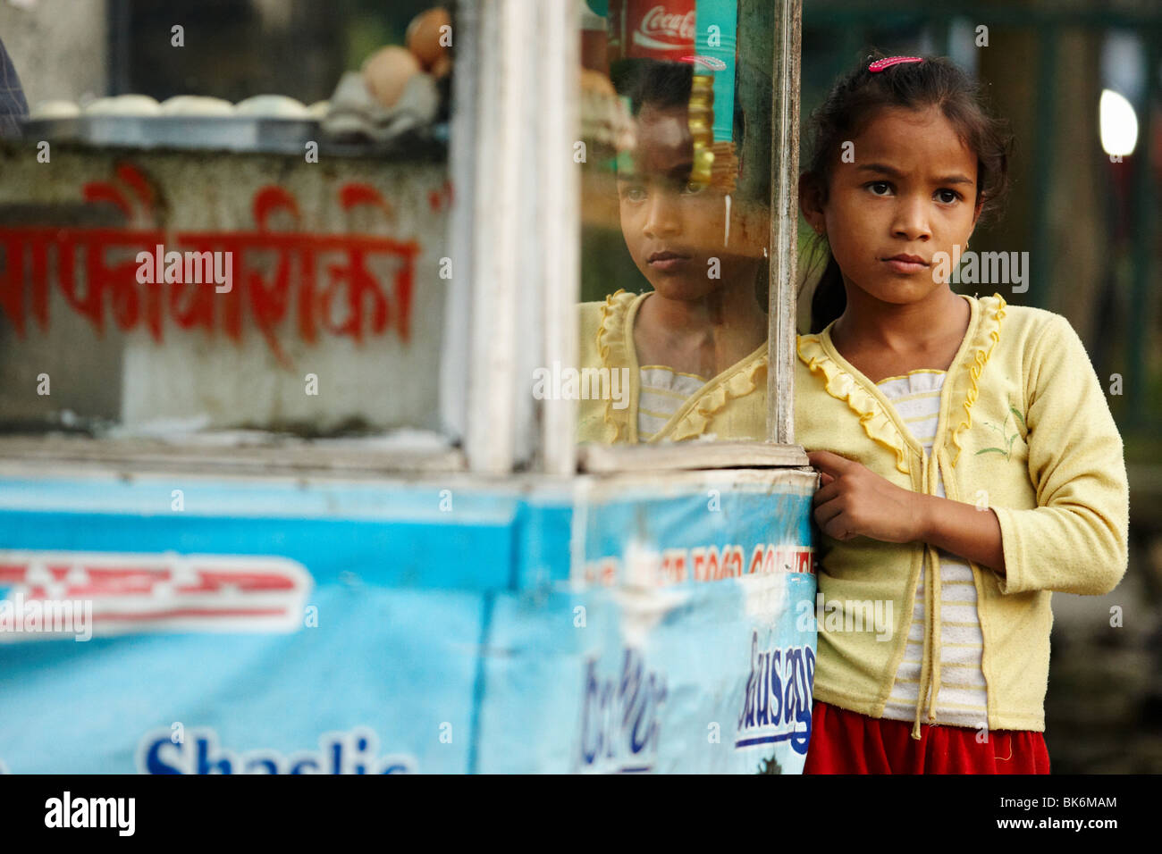 A girl stands by a stall selling snacks in Pokhara, Nepal on Monday October 26, 2009. - Stock Image