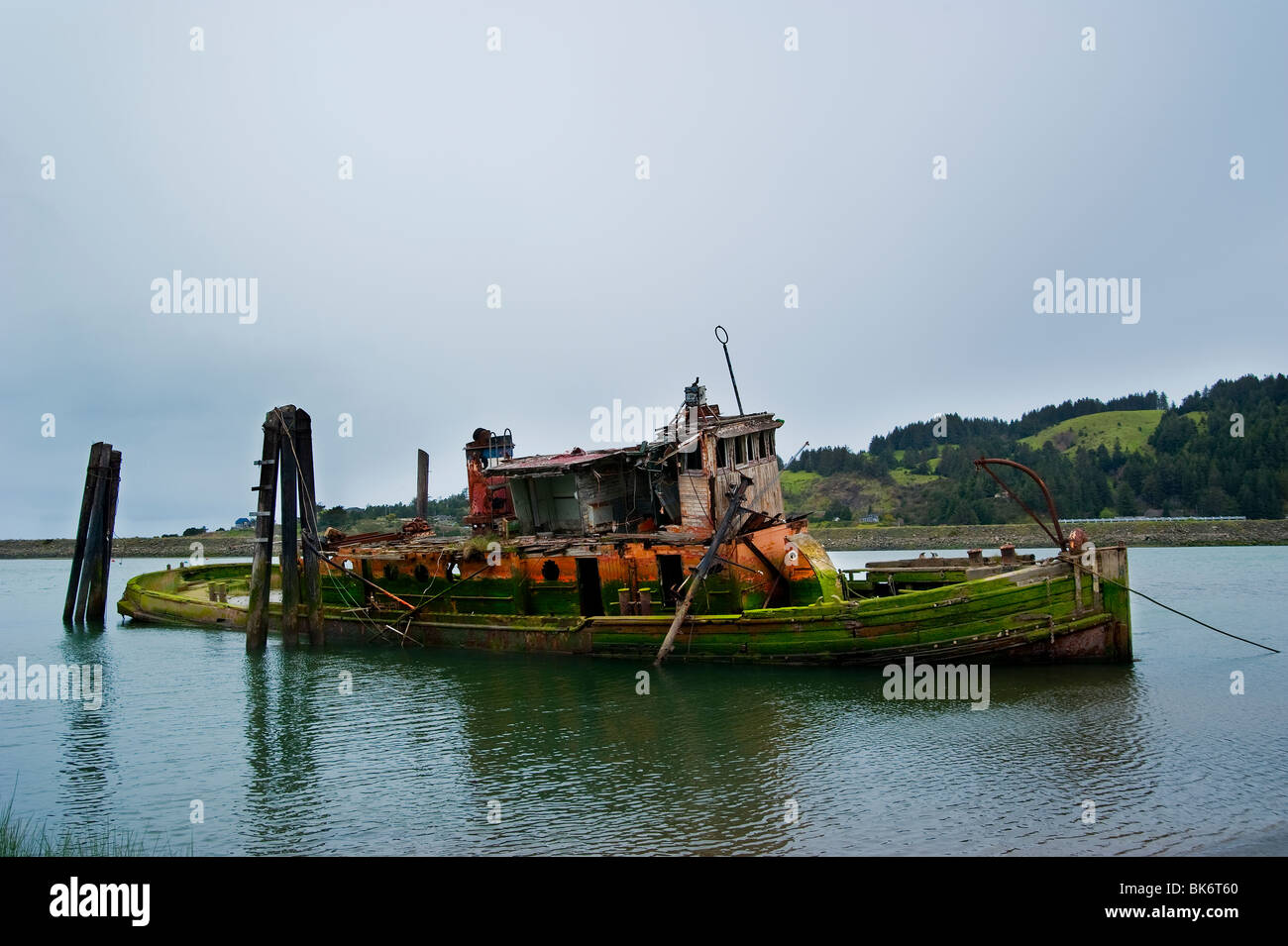 Old weathered boat anchored in a bay - Stock Image