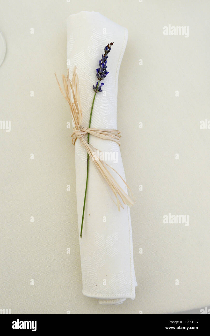 White napkin with lavender flower, rolled and tied with raffia. - Stock Image