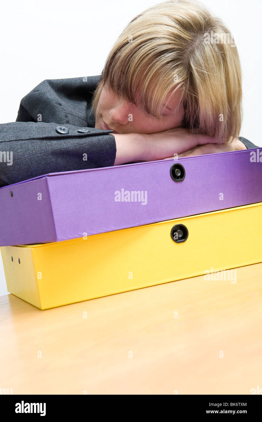 tired female office worker sleeping on box files - Stock Image