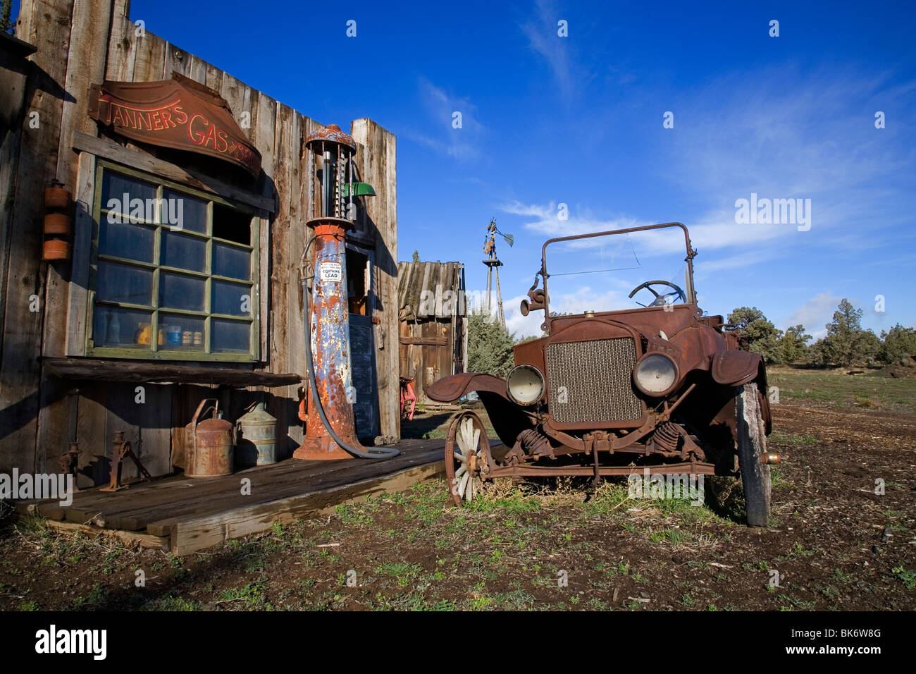 An ancient rusted antique car, gasoline pump, and gasoline station - Stock Image