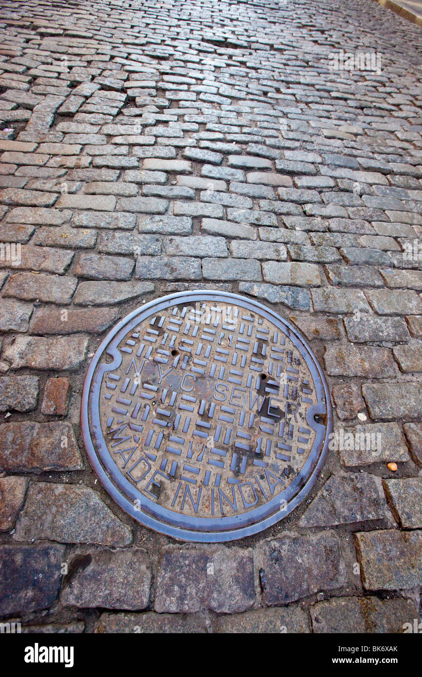 New York sewer cover on a cobblestone street in Tribeca, Manhattan, New York - Stock Image