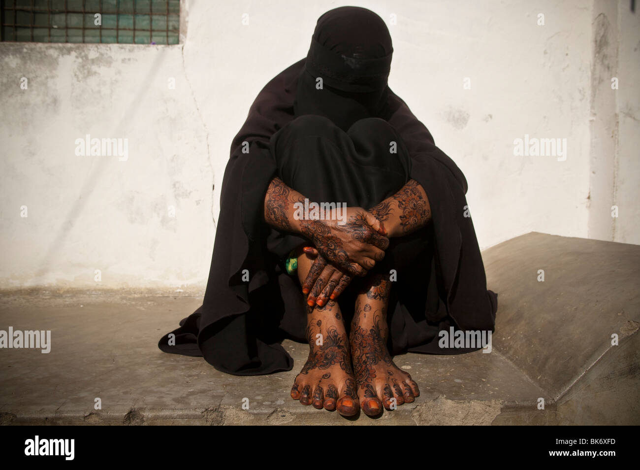 A woman wearing a burqa shows her henna body paint in the town of Lamu island on August 17, 2009, Kenya. - Stock Image