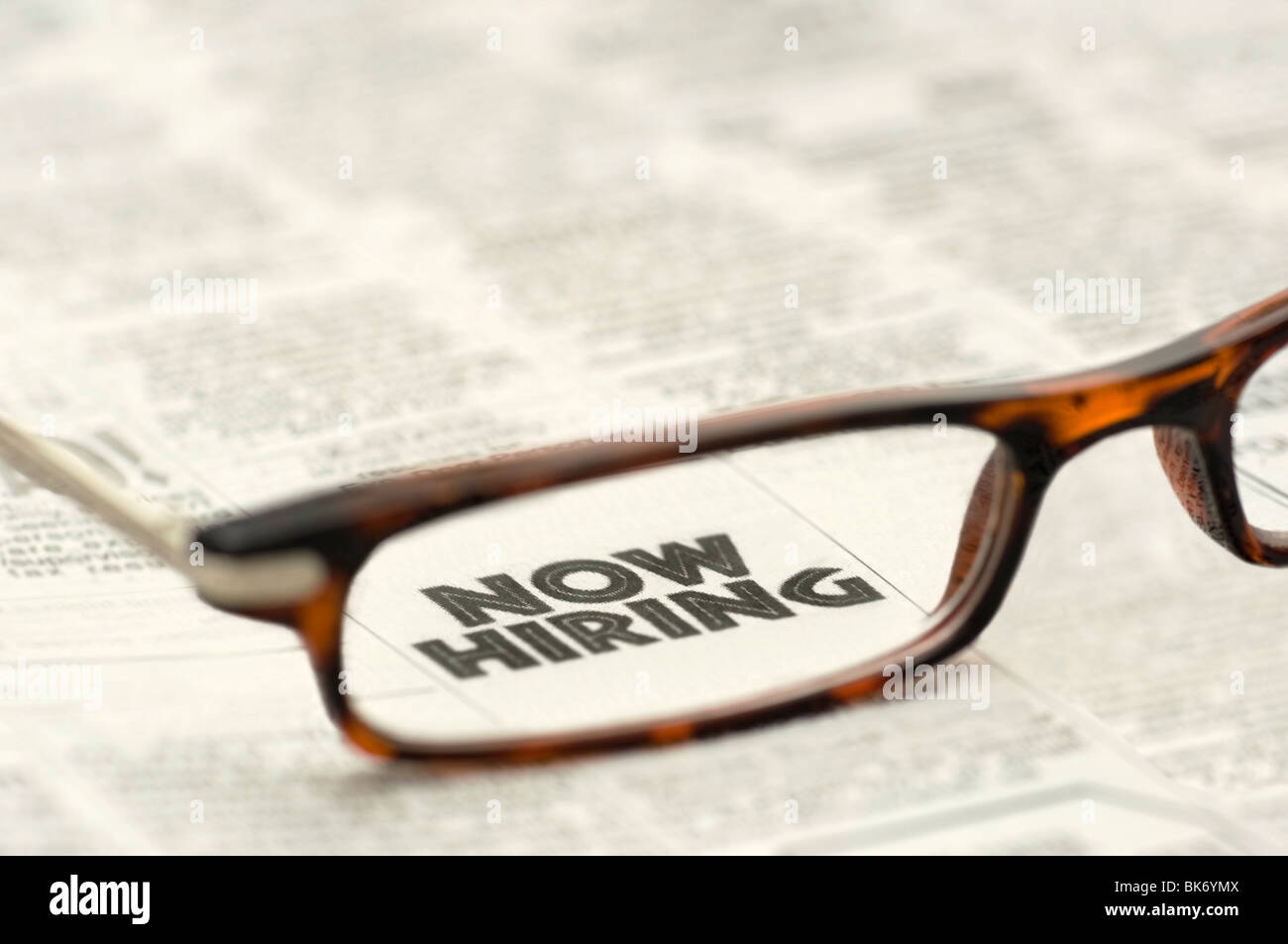 Now Hiring classified ad showing through reading glasses. - Stock Image