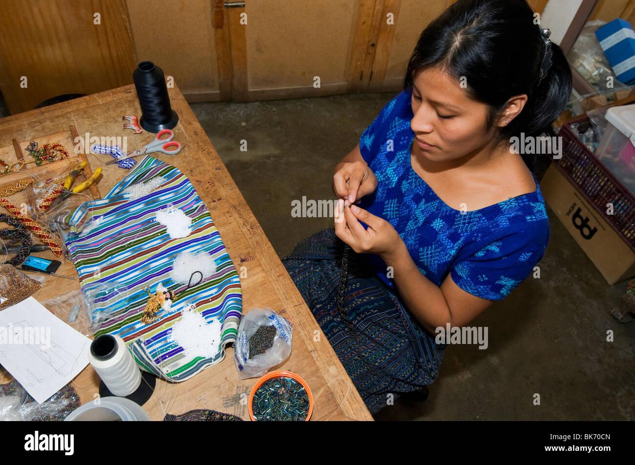Indigenous female workers making handmade jewelery  from beads Santiago de Atitlan Guatemala - Stock Image