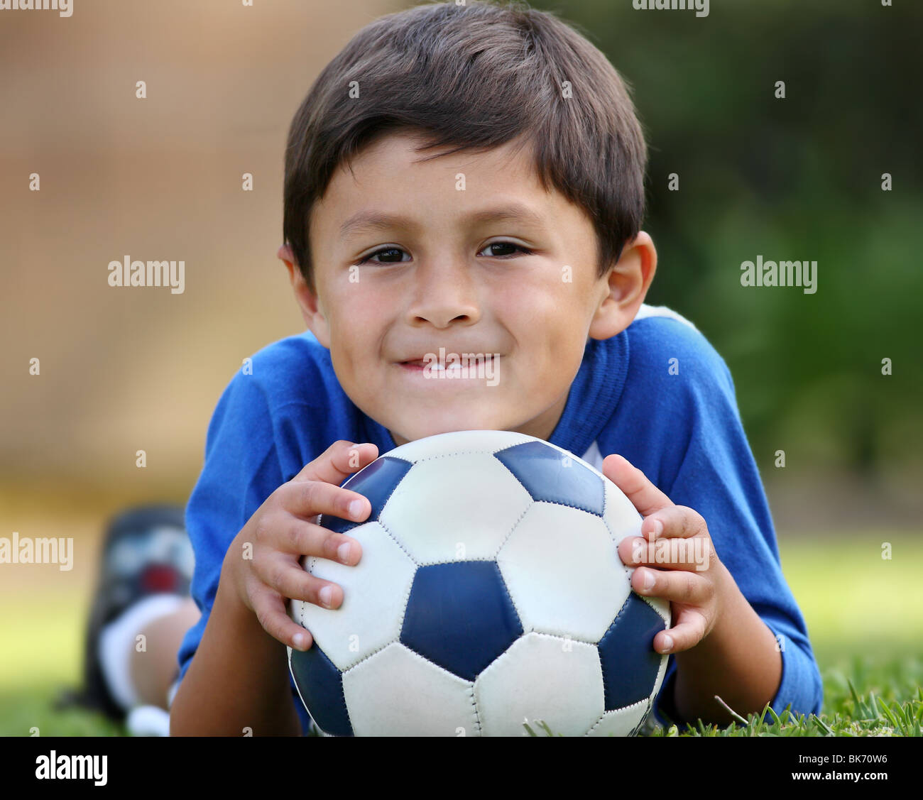 Young brown haired hispanic boy in blue shirt lying down on grass with soccer ball in hands - Stock Image