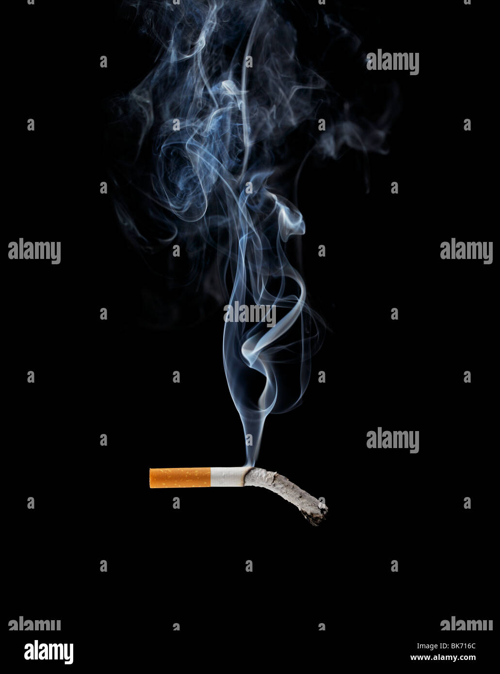 A Smoking cigarette on black background - Stock Image
