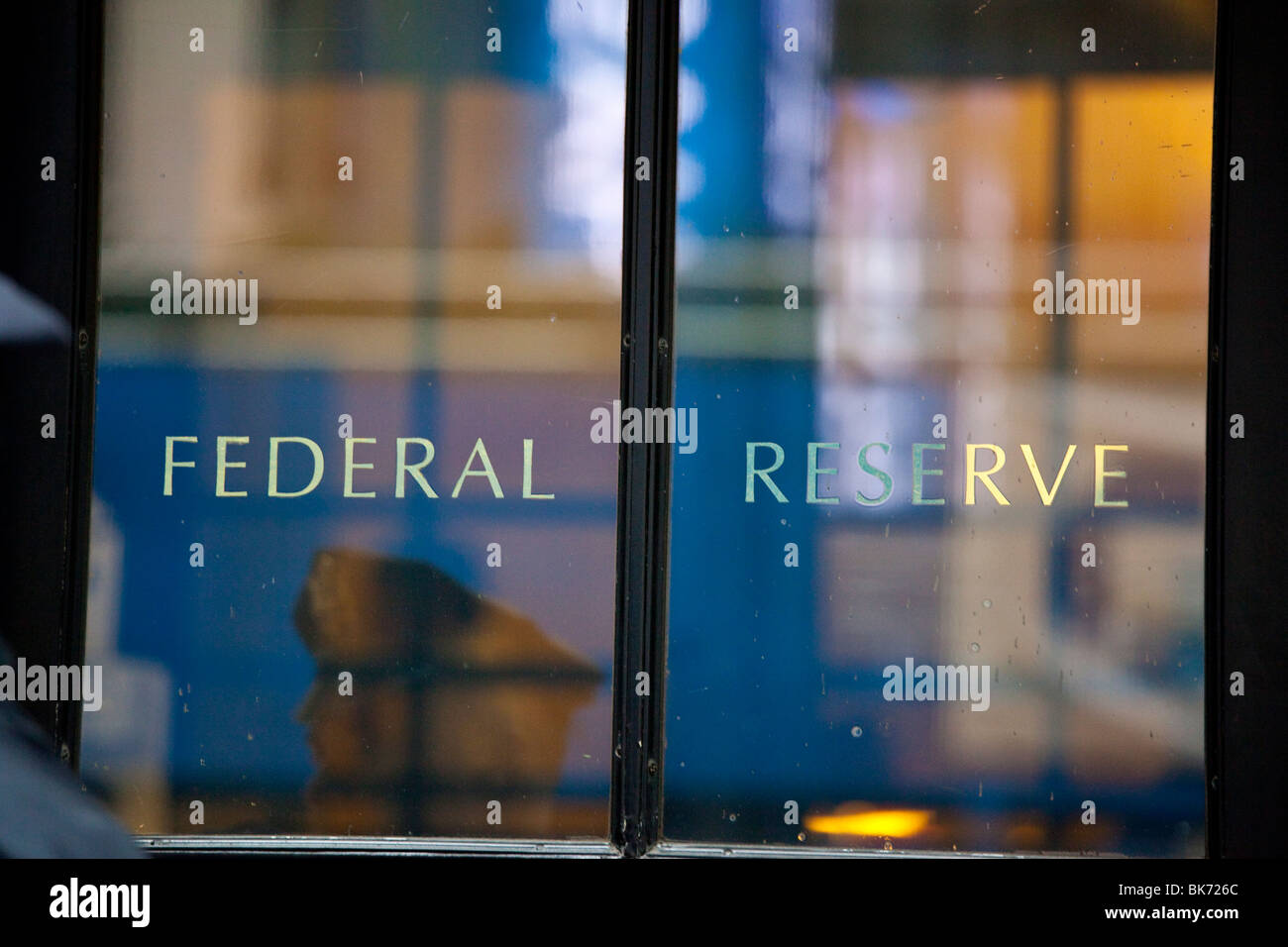 Security guard reflection in the door of the Federal Reserve