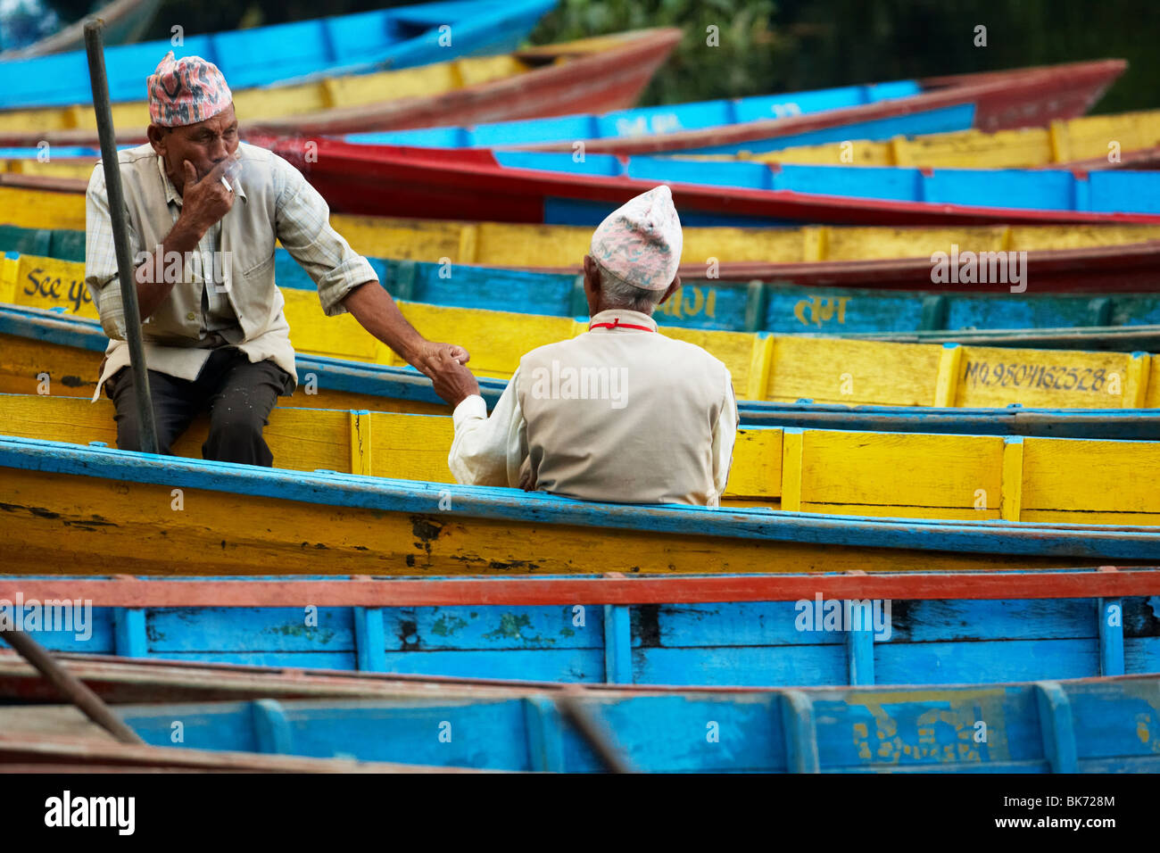 Two old men sitting on row boats share a cigarette in Pokhara, Nepal. - Stock Image