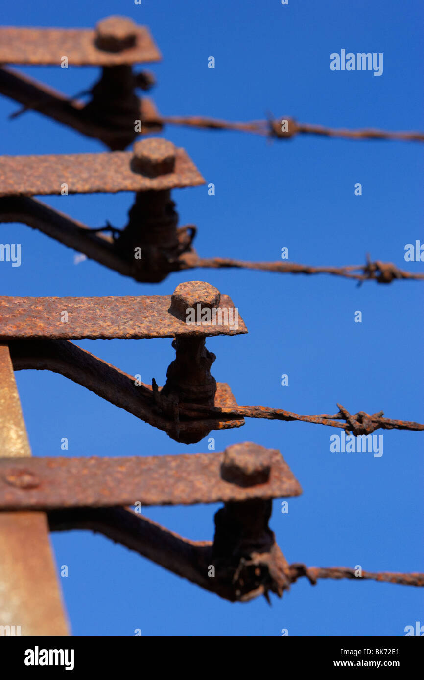 old rusty rusted end posts tensioners of a barbed wire security fence against a blue sky - Stock Image