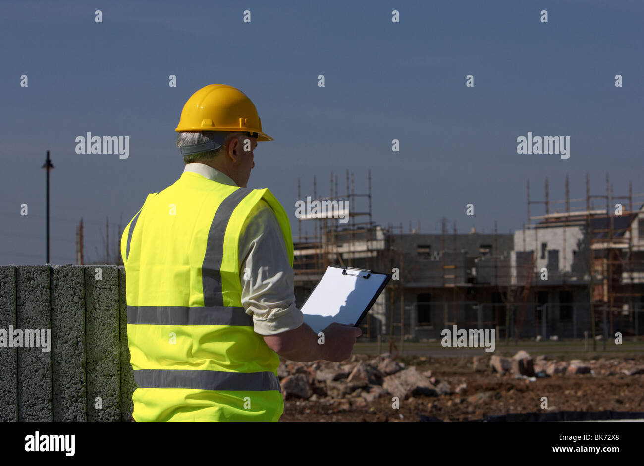 middle aged grey haired man wearing hard hat and hivis vest holding a clipboard building blocks on construction - Stock Image