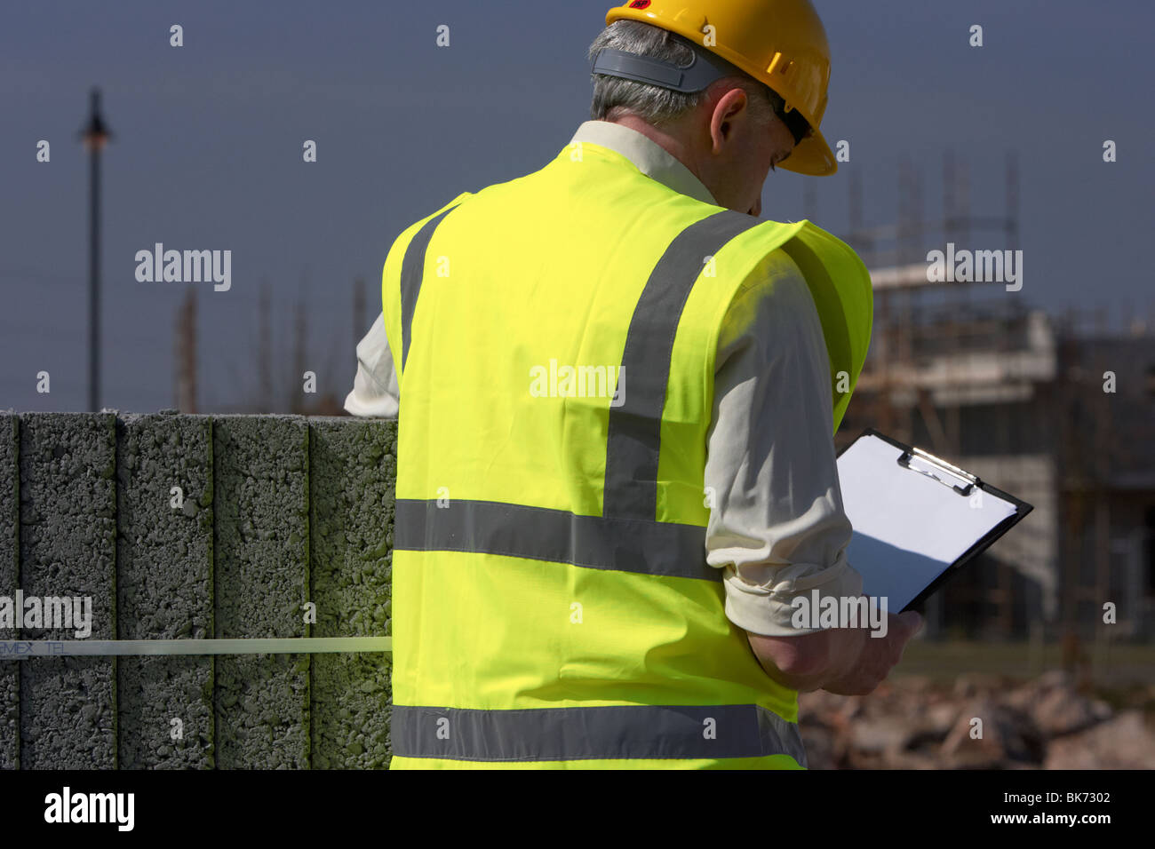 middle aged grey haired man wearing hard hat and hivis vest holding and looking down at a clipboard reviewing plans - Stock Image