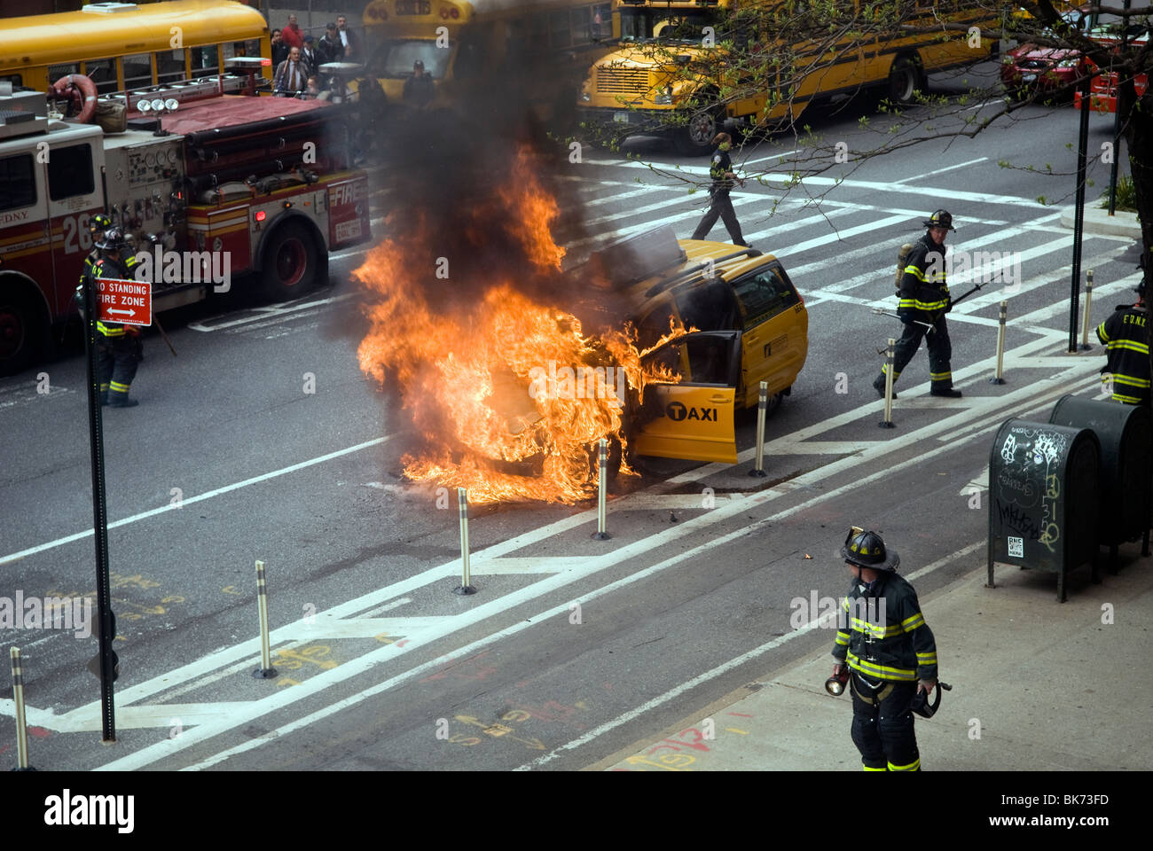 Members of the FDNY extinguish a taxicab that has caught fire on Ninth Avenue in the New York neighborhood of Chelsea - Stock Image