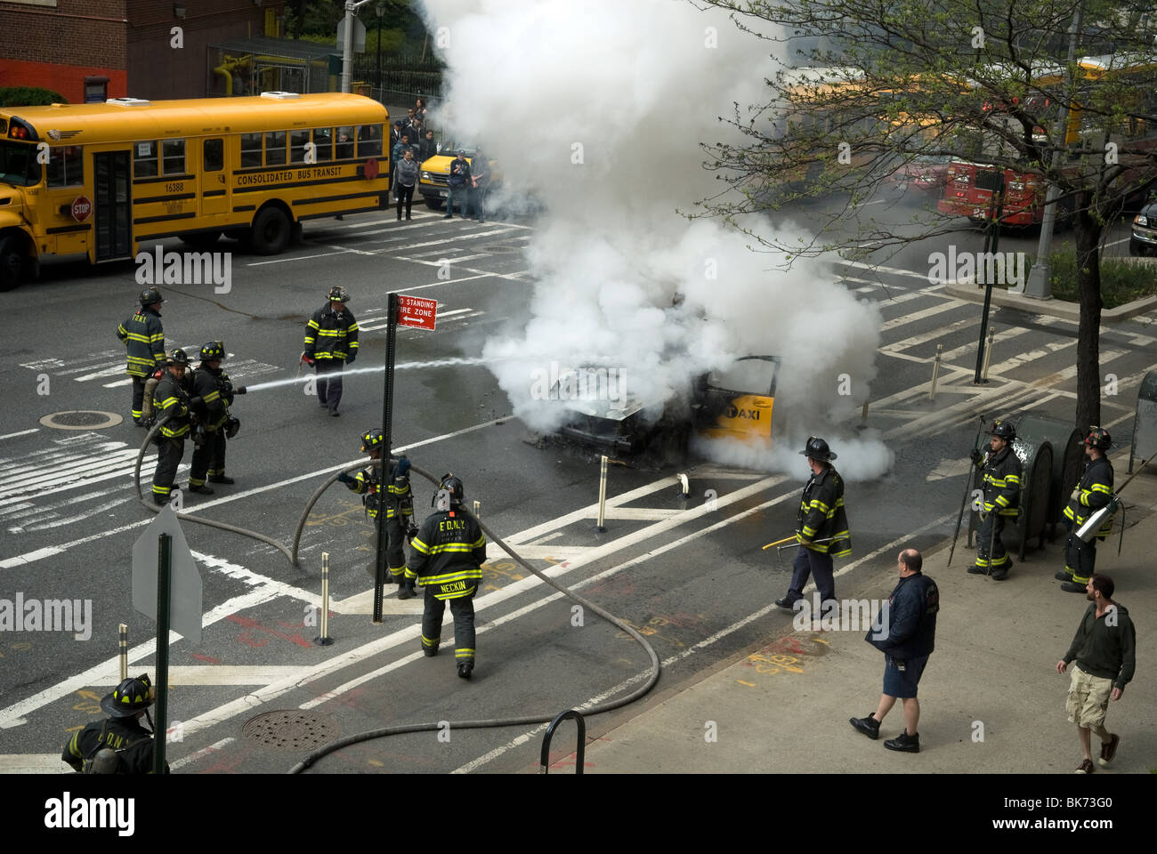 Members of the FDNY extinguish a taxicab that has caught fire on Ninth Avenue in the New York neighborhood of Chelsea Stock Photo